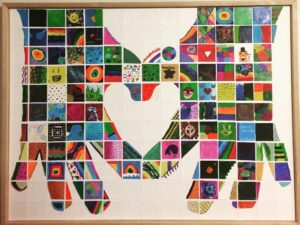 Photo of a colorful mosaic of artwork, showing hands forming a heart.