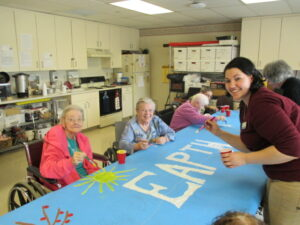 """A group of elderly participants with an assistant, painting a mural. The word """"Earth"""" is seen on the mural and participants are smiling."""