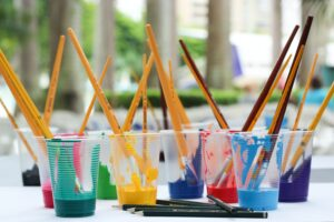 Photo of clear plastic cups filled with different colors of paint and paintbrushes.