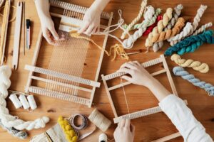 Image of two sets of hands working on weaving projects.