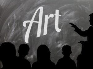 """Black and white image of the word """"Art"""" on a blackboard with outline of teacher and students in foreground"""