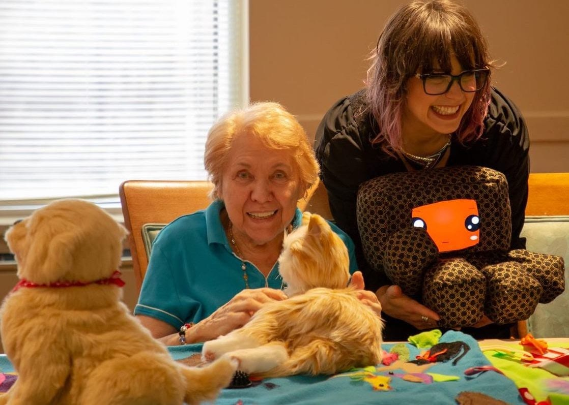 elderly woman interacting with a social robotic cat while therapist/roboticist engages with elderly using social robot FAMbot