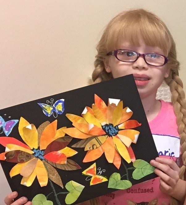 Image of young girl proudly showing her collage flower art.