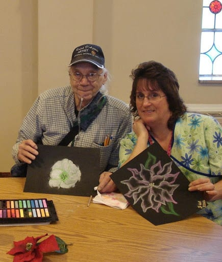 Elderly man with aide showing their artwork.