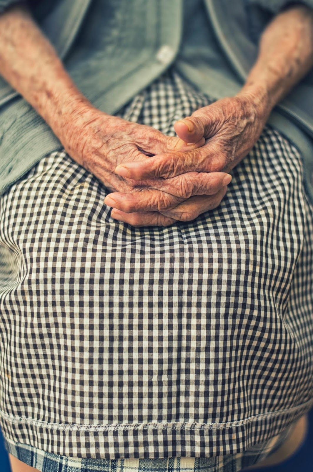 Photo of Elderly Hands Folded in a Lap