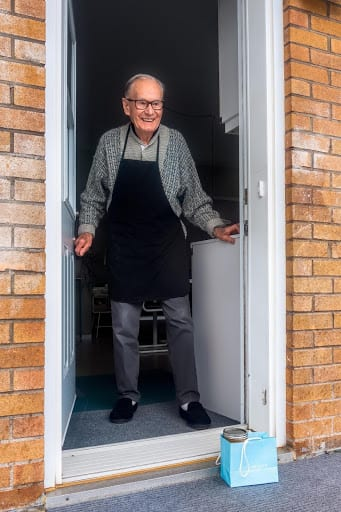 Photo of an elderly man receiving a gift at his door. He has a smile on his face.